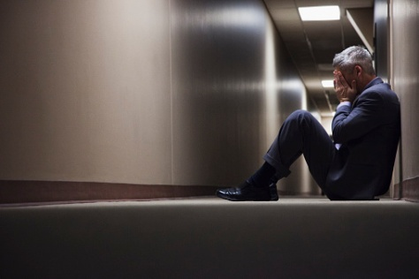 Businessman sitting on floor in corridor | Credit: Blend_Images
