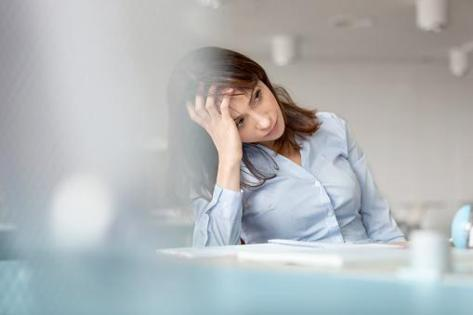 Tired businesswoman with head in hands looking away | Credit: Caiaimage/Agnieszka Wozniak