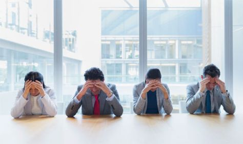 Stressed business people with heads in hands | Credit: Caiaimage/Robert Daly