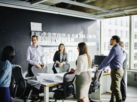 Businesspeople beginning meeting in office | Credit: Thomas Barwick